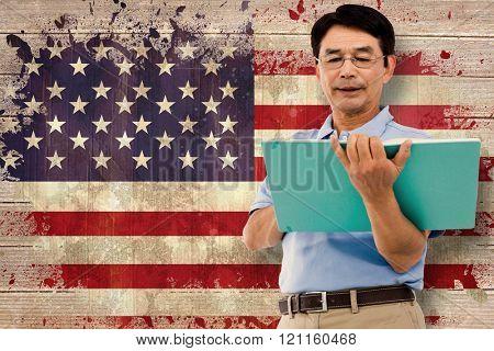 Elderly man holding a green folder against usa flag in grunge effect