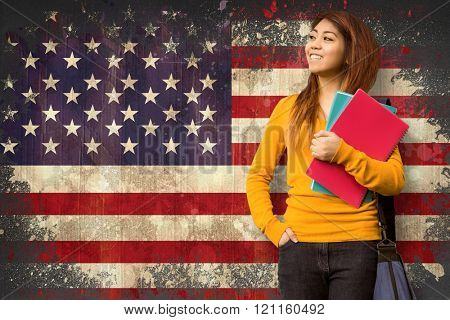 Female college student with books in park against usa flag in grunge effect