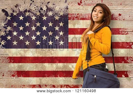 Female college student with bag in park against usa flag in grunge effect