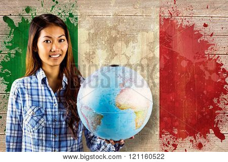 Smiling asian woman holding a globe against italy flag in grunge effect