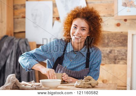 Cheerful young woman potter with curly red hair in apron sitting and working in art pottery studio