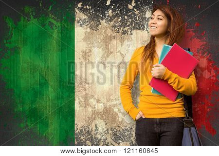Female college student with books in park against italy flag in grunge effect