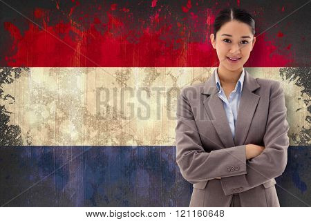 Portrait of a smiling brunette businesswoman posing with the arms crossed against netherlands flag in grunge effect