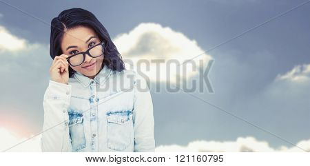 Asian woman holding eyeglasses against beautiful blue cloudy sky