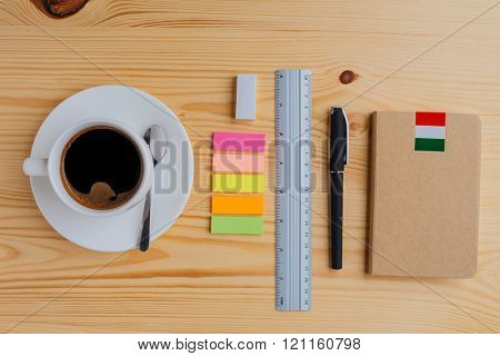 Top view of office supplies and cup of coffee on the table