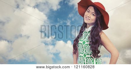 Asian woman with hat posing for camera against blue sky with white clouds