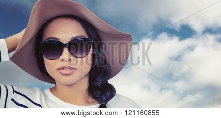 Attractive Asian woman with hat and sunglasses against blue sky with clouds