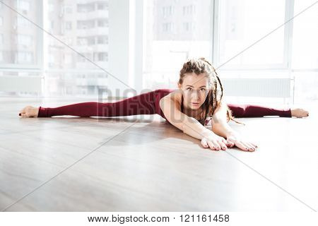 Pretty young woman with dreadlocks lying on the floor and doing twine