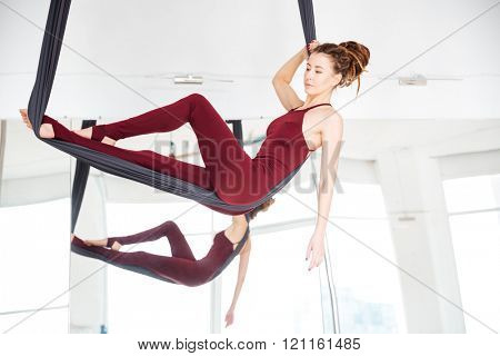Pensive young woman doing antigravity yoga using hammock over the mirror