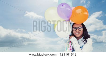 Asian woman holding colorful balloons against blue sky