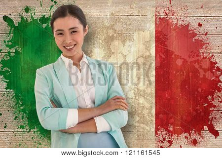 Smiling businesswoman with folded arms against italy flag in grunge effect