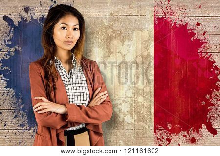 Businesswoman with crossed arms against france flag in grunge effect