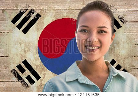 Portrait of a smiling businesswoman against korea republic flag in grunge effect
