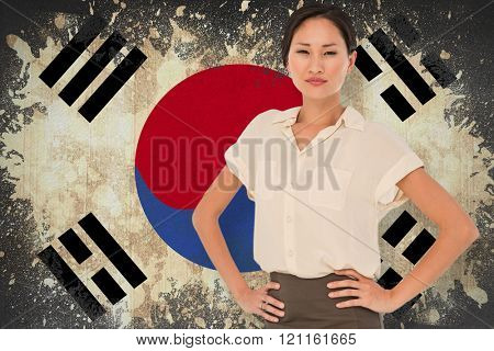 Asian businesswoman with hands on hips against korea republic flag in grunge effect