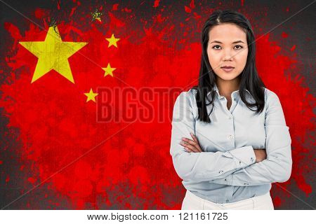 Woman with arms crossed looking at camera against china