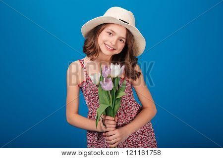 Portrait of lovely smiling little girl in hat with bouquet of flowers over blue background