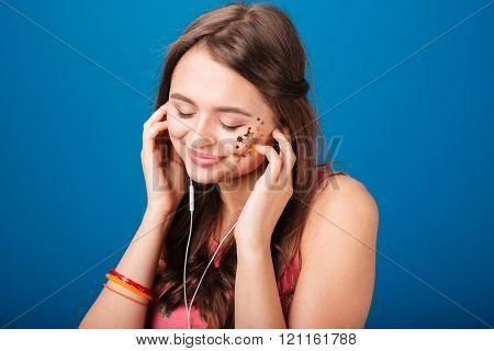 Beautiful tender young woman listening to music using earphones over blue background