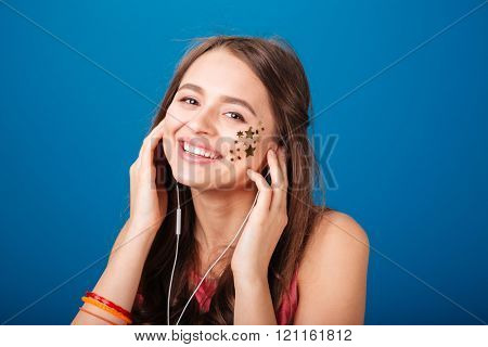 Cheerful pretty young woman with star shaped decoration on cheek listening to music over blue background