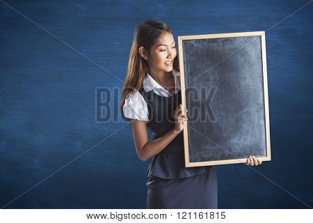Smiling businesswoman holding a blackboard against blue chalkboard