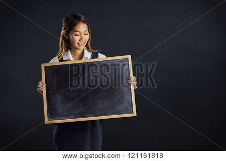 Smiling businesswoman holding a blackboard against black background