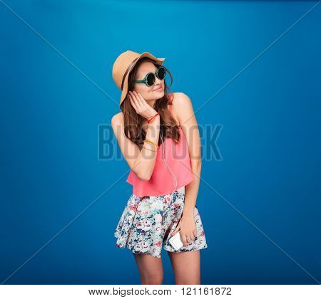 Happy pretty young woman listeting to music from smartphone using earphones over blue background