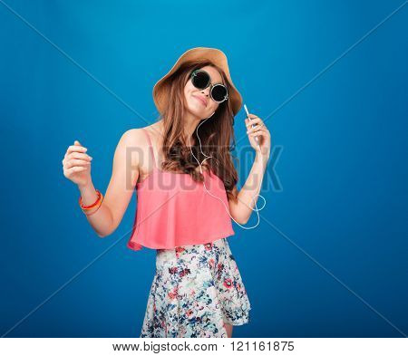 Smiling attrative young woman in hat and sunglasses listening to music from cell phone over blue background