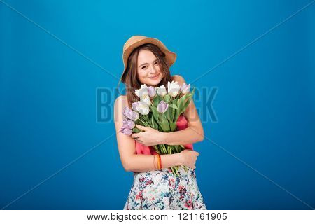 Smiling pretty young woman holding bouquet of flowers over blue background