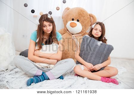 Two sad tired sisters sitting and hugging pillows in children room at home
