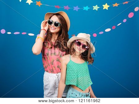 Two cheerful beautiful sisters in hats and sunglasses standing and posing over blue background