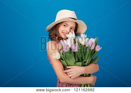 Smiling beautiful little girl in hat standing and holding bouquet of tulips over blue background