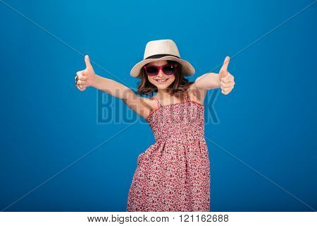 Lovely happy little girl in hat and sunglasses showing thumbs up with both hands over blue background