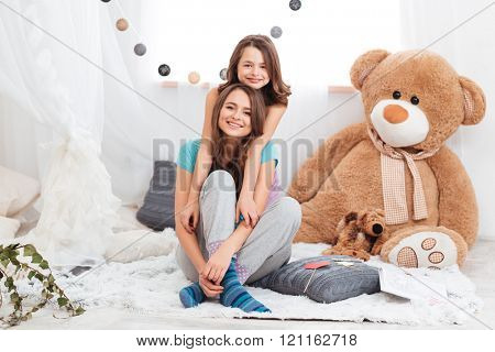 Two smiling beautiful sisters sitting together in children room