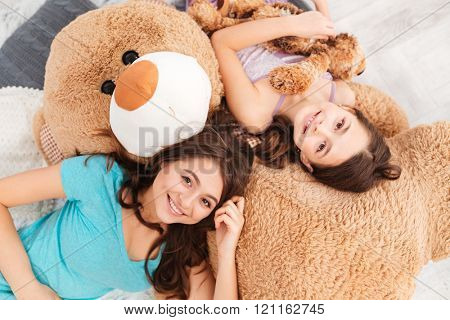 Top view of two smiling beautiful sisters lying on big soft plush bear in children room