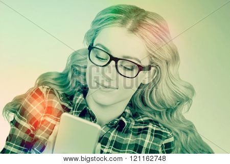 Gorgeous smiling blonde hipster using smartphone against green background