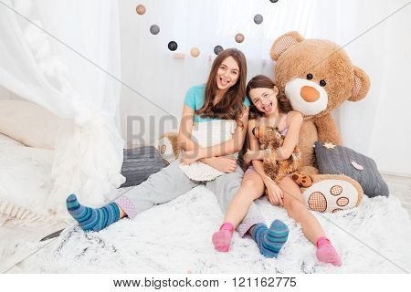 Two funny lovely sisters sitting and showing tongues in children room