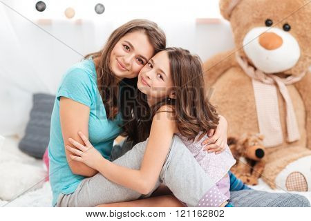 Two cute lovely sisters sitting and hugging in children room