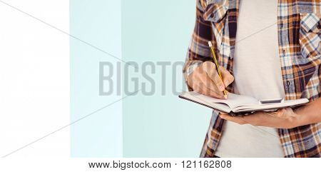 Mid section of hipster writing with pencil on book against blue background