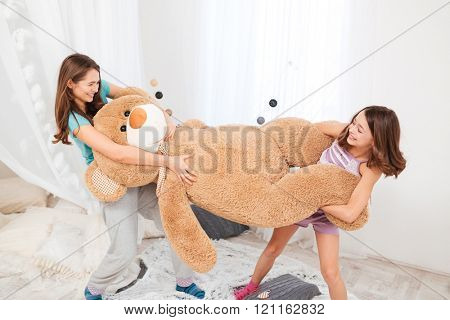 Two cheerul playful sisters playing and having fun with big plush bear at home