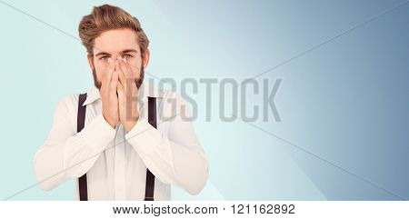 Portrait of hipster with hands covering mouth against blue background