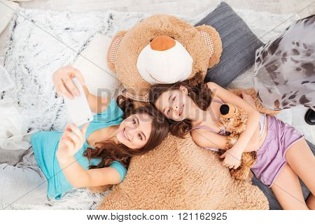 Top view of two happy beautiful sisters lying on big plush bear and taking selfie with mobile phone at home