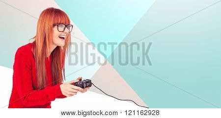 Smiling hipster woman playing video games against orange background