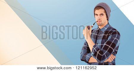 Portrait of hipster holding smoking pipe against blue vignette background