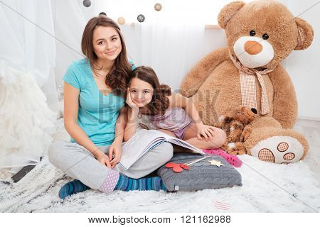 Portrait of two beautiful smiling sisters sitting in children room together