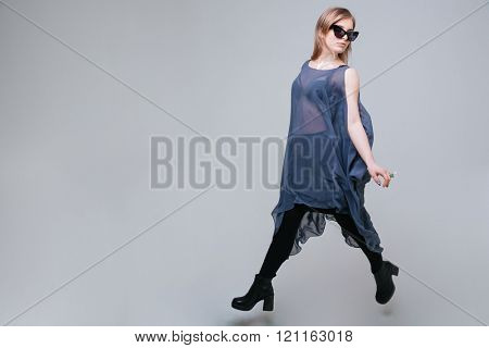 Full length portrait of a fashion woman walking over gray background