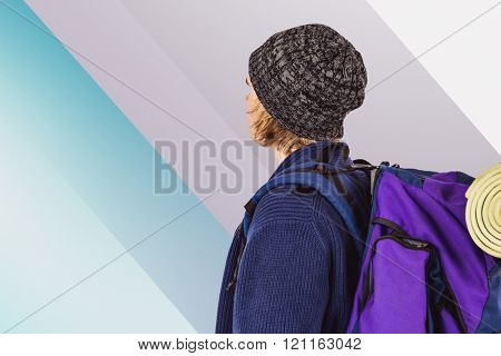 Side view of backpacker hipster against colored background