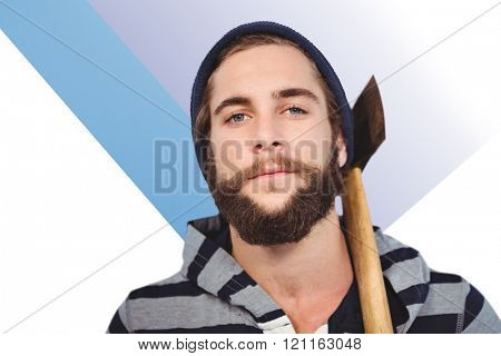 Close-up portrait of hipster with hooded shirt holding axe against colored background