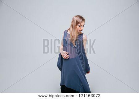 Stylish female model posing over gray background