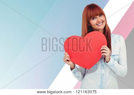 Attractive hipster woman behind a red heart against colored background