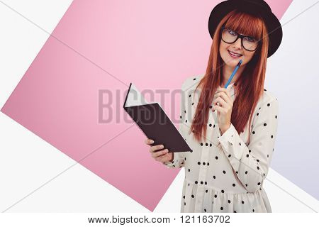 Attractive hipster woman writing on notepad against rosa and white