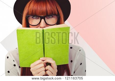 Hipster woman behind a green book against rosa beige and white